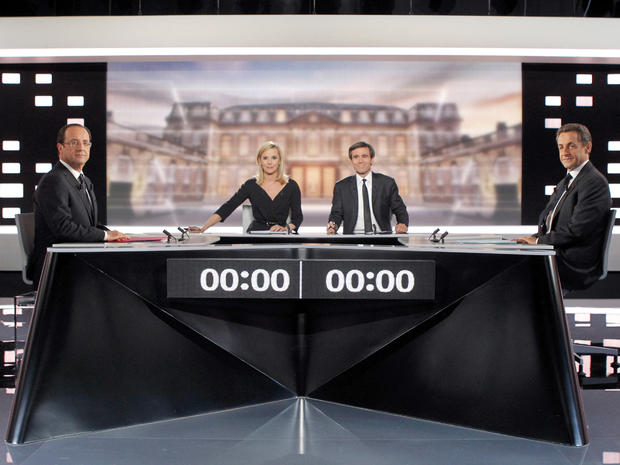 Socialist Party candidate for France's presidential election Francois Hollande, left, and conservative incumbent Nicolas Sarkozy, right, pose before a televised debate in Paris May 2, 2012. At center are television hosts Laurence Ferrari, second left, and David Pujadas.