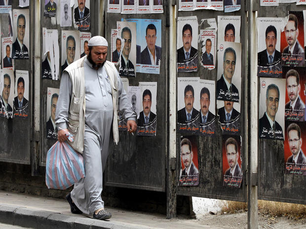 Syrian man walks past campaign posters for the upcoming parliamentary election