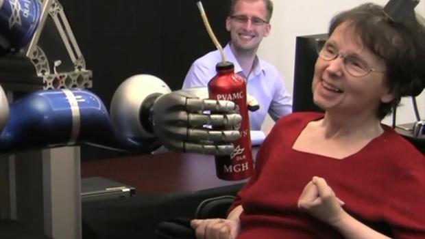 Paralyzed woman operates robotic arm