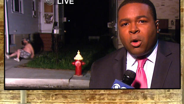 In the middle of WCBS reporter Derricke Dennis' live shot, a man falls from a first-story window.
