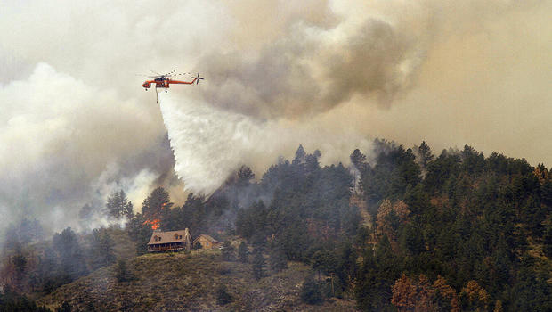 firefighting helicopter drops water on a hotspot burning close to homes