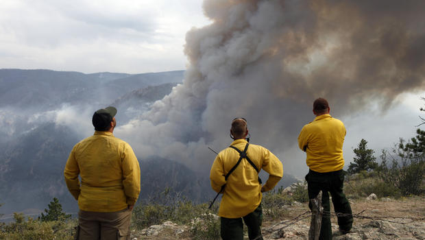 Firefighters watch as flames leap hundreds of feet in air as High Park wildfire fire explodes on south side of Poudre Canyon west of Fort Collins, Colo. Thursday