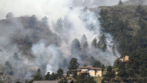 Fire burns in trees behind homes on the High Park wildfire near Fort Collins, Colo., on Monday, June 11, 2012. The wildfire is burning out of control in northern Colorado, while an unchecked blaze choked a small community in southern New Mexico as authori