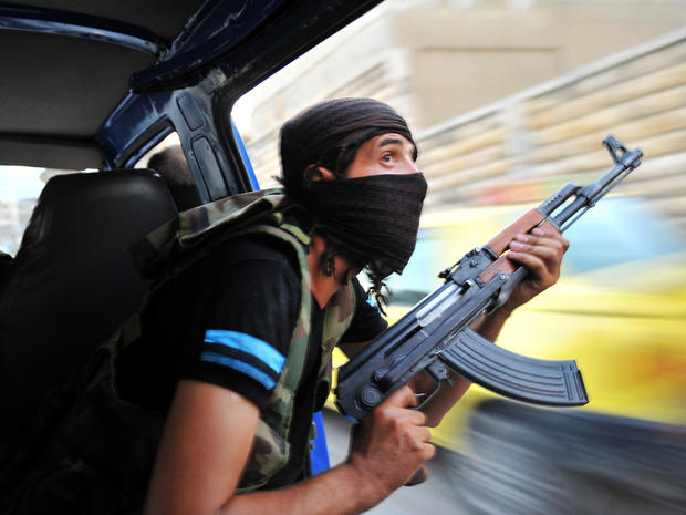 Syrian rebels hunt for snipers after attacking the municipality building in the city center of Selehattin, Syria, July 23, 2012, during fights between rebels and Syrian troops.