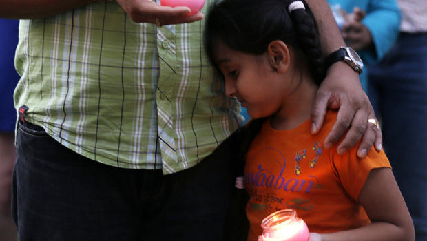 A man holds his child during a candlelight vigil in Milwaukee Aug. 5, 2012, for the victims of the Sikh Temple of Wisconsin shooting.