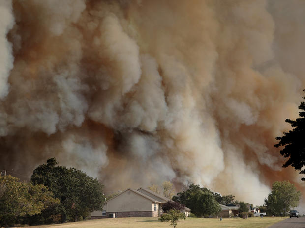 A wildfire burns near homes in Luther, Okla.