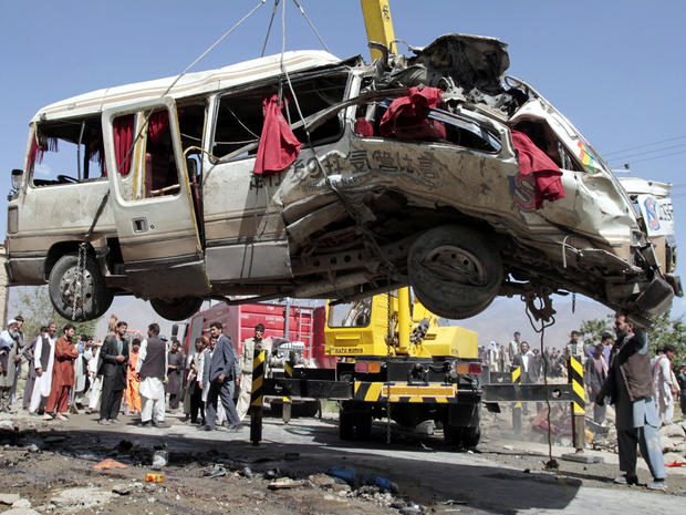 A damaged bus that was hit by a remote-controlled bomb is lifted by a crane on the outskirts of Kabul, Afghanistan, Aug. 7, 2012.