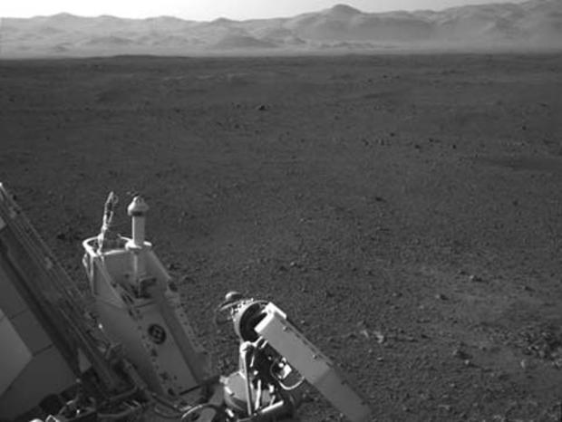 This full-resolution image shows part of the deck of NASA's Curiosity rover taken from one of the rover's Navigation cameras looking toward the back left of the rover. On the left of this image, part of the rover's power supply is visible. To the right of the power supply can be seen the pointy low-gain antenna and side of the paddle-shaped high-gain antenna for communications directly to Earth. The rim of Gale Crater is the lighter colored band across the horizon. The effects of the descent stage's rocket engines blasting the ground can be seen on the right side of the image, next to the rover.