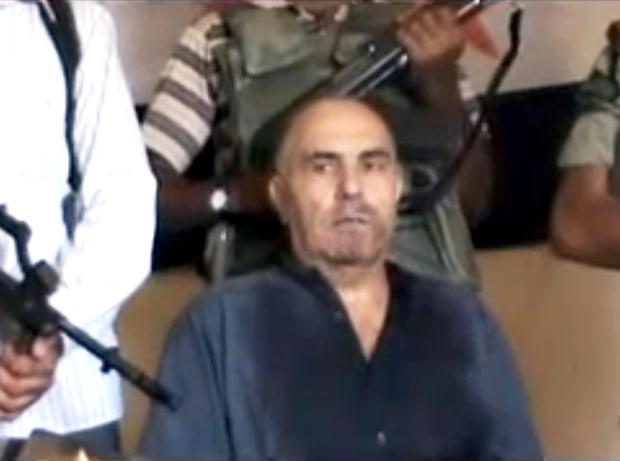 An image from an amateur video released by the Shaam News Network purports to show Syrian Pilot Colonel Rafik Mohammed Suleiman being interrogated by rebel officers after his Soviet-made MiG warplane was apparently hit by ground fire over Deir el-Zour province, an area near the Iraqi border, Syria, Monday Aug. 13, 2012.