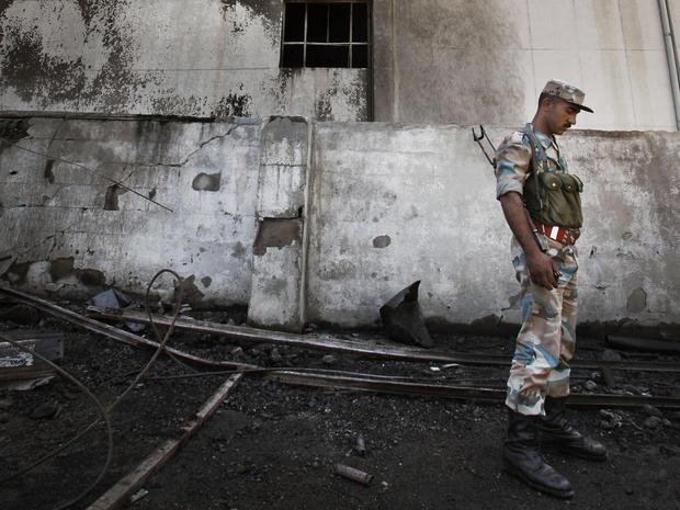 Syrian soldier investigates the scene of a bomb blast