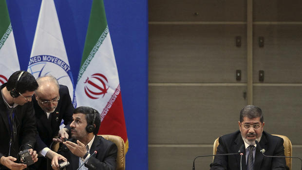 Egyptian President Mohammed Morsi, right, addresses a summit of the Non-Aligned Movement as Iranian President Mahmoud Ahmadinejad, left, confers with other Iranian officials