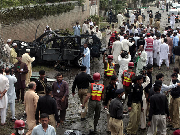 Officials and rescue volunteers gather at the bombing site in Peshawar