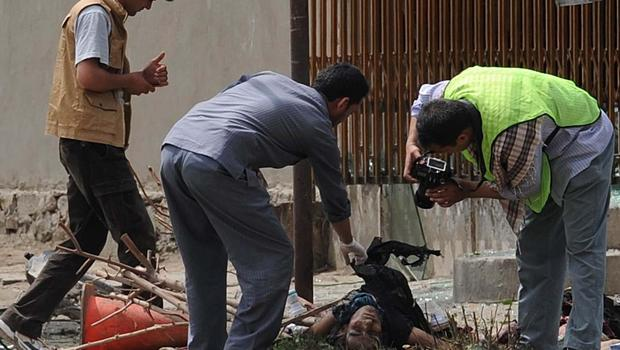 Afghan investigators inspect remains of suicide attack victim in Kabul Saturday