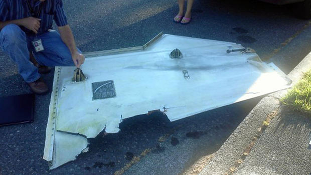Man examines piece of metal that appears to be a landing gear door that fell from plane in Kent, Wash. Friday
