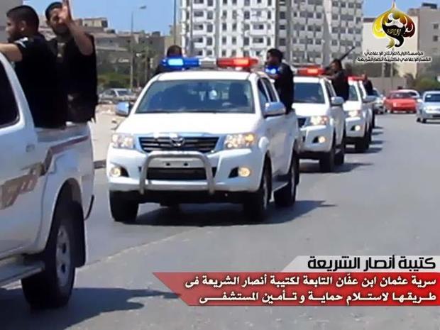 Militants from the Libyan Ansar al-Sharia group drive through Benghazi