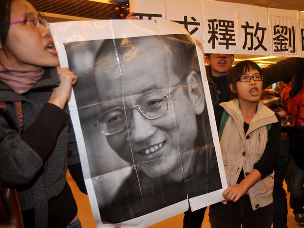 Demonstrators hold a portrait of China's detained Nobel Peace Prize winner Liu Xiaobo