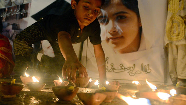 A Pakistani youth places an oil lamp next to a photograph of child activist Malala Yousafzai, who was shot in the head in a Taliban assassination attempt, during a tribute in Karachi, Pakistan, Oct. 12, 2012.