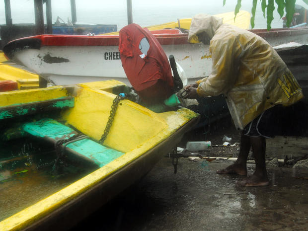 Fisherman Hubert Dowie works to secure his boat before the arrival of Hurricane Sandy in Port Royal, Jamaica, Oct. 24, 2012.