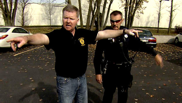 Lt. Brian Murphy, front, and Officer Sam Lenda demonstrate what happened during an August morning shootout in the parking lot of a Sikh temple in Wisconsin. Six people were killed, and Murphy was shot 12 times.