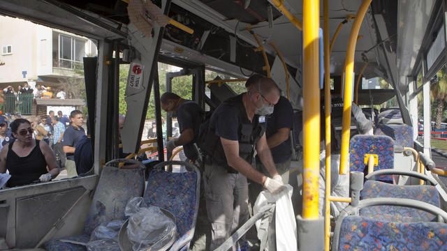 Israeli police officers examine a bus destroyed by a bomb in Tel Aviv