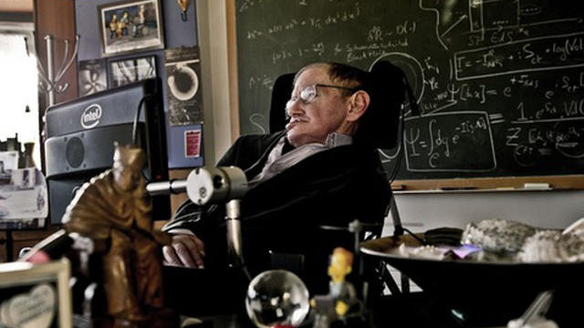 A photograph of Stephen Hawking in his office, surrounded by some of the memorabilia now on display at the Science Museum.