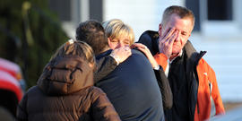 Unidentified people react on December 14, 2012 at the aftermath of a school shooting at a Connecticut elementary school that brought police swarming into the leafy neighborhood, while other area schools were put under lock-down, police and local media said. Local media quoted that the gunman had died at the Sandy Hook Elementary School in Newtown, Connecticut, northeast of New York City. At least 27 people, including 18 children, were killed on Friday when at least one shooter opened fire at an elementary school in Newtown, Connecticut, CBS News reported, citing unnamed officials.