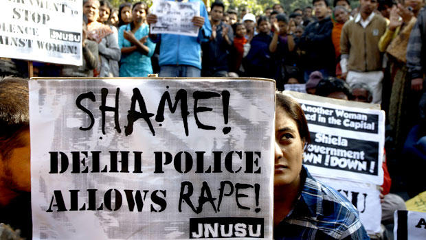 An Indian woman along with the others participates in a protest condemning the gang rape of a 23-year-old student on a city bus late Sunday in New Delhi, India, Tuesday, Dec. 18, 2012.