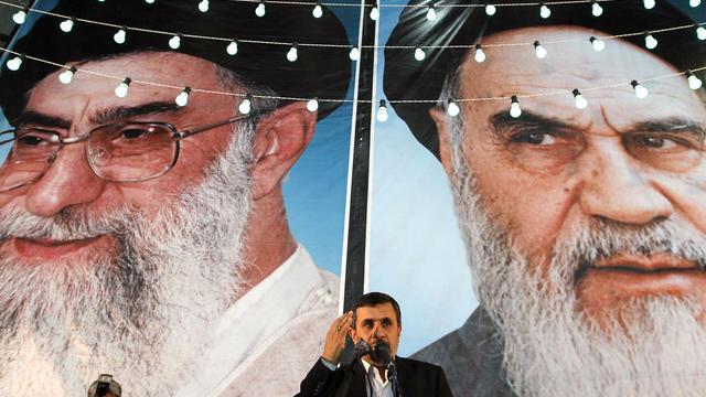 President Mahmoud Ahmadinejad delivers a speech under portraits of Iran's supreme leader, Ayatollah Ali Khamenei (L) and founder of the Islamic Republic of Iran, Ayatollah Ruhollah Khomeini