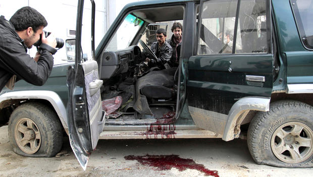 An Afghan intelligence officer, center, tries to turn on a vehicle used by an insurgent, who was killed by security forces, in Kabul, Afghanistan, Sunday, Feb. 24, 2013.