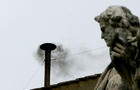 Black smoke rises from a chimeny on the Sistine Chapel