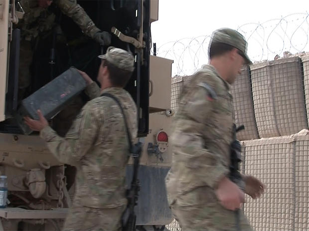 U.S. soldiers load boxes onto a truck as they prepare to leave Combat Outpost Timothy Johnson