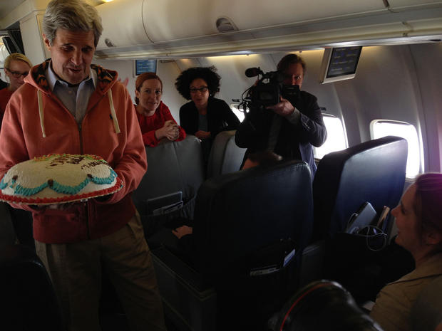U.S. Secretary of State John Kerry presents a birthday cake to CBS News State Department correspondent Margaret Brennan, as they marked her birthday while flying from Kabul, Afghanistan, to Paris, France, March 26, 2013.