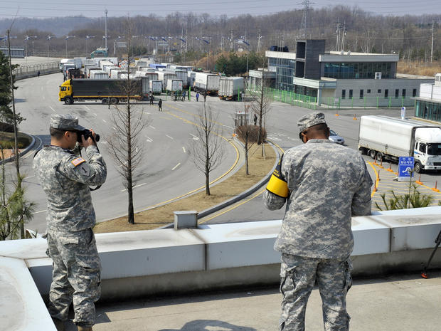 U.S. soldiers take pictures as South Korean trucks turn back at a border crossing in Paju