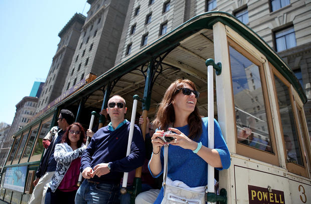 Passengers ride a cable car as it travels along Powell Street on June 9, 2011 in San Francisco, California.