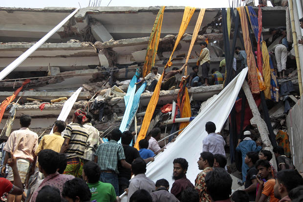 Rescue workers use long swathes of cloth to bring down survivors and bodies after an eight-story building collapsed