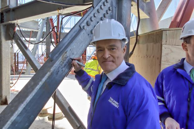 Scott Pelley signs a steel beam on the roof of One World Trade Center.