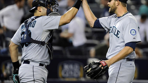 Seattle Mariners pitcher Tom Wilhelmsen celebrates with catcher Jesus Montero after defeating the New York Yankees 3-2 in a baseball game May 16, 2013, at Yankee Stadium in New York.