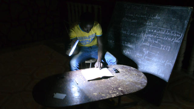 A student does his homework on June 18, 2013, with a flashlight in Niamey, the capital of Niger, during an electrical blackout.