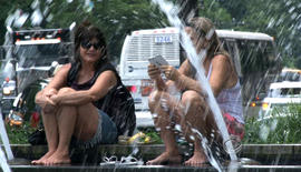 New Yorkers relax by a fountain on July 16, 2013, where temperatures reached 95 degrees.