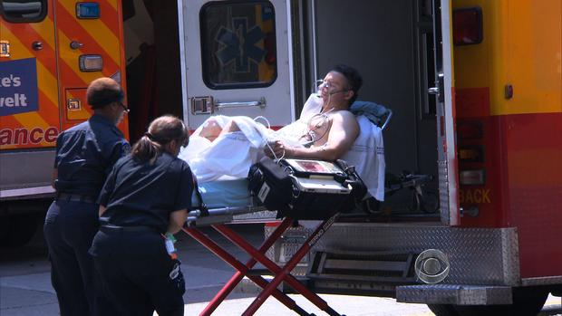 EMT workers with St. Luke's-Roosevelt hospital attend to a man during a brutal heat wave in New York City July 17, 2013.