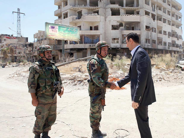 Syrian President Bashar Assad purportedly shakes hands with a solider during Syrian Arab Army day in Darya, Syria, in this image posted on the official Facebook page of the Syrian Presidency Aug. 1, 2013.