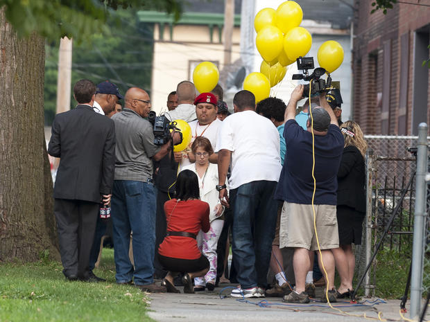 Michelle Knight, center, talks with reporters Aug. 7, 2013, outside the home of Ariel Castro in Cleveland.