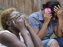 Carolyn Webb, left, sits with Sonya Ellington near the house where their friend was killed in a fatal multiple shooting Aug. 8, 2013, in DeSoto, Texas.