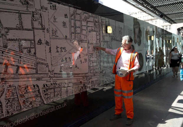 A member of the the archaeological team from the Museum of London points to the present day position of London's Liverpool Street Station on a 16th century map of the city