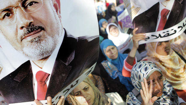 """Supporters of ousted Egyptian President Mohammed Morsi hold posters with Morsi's face and words in Arabic that read """"No to the coup"""" as they march in the Maadi district of Cairo Aug. 19, 2013."""