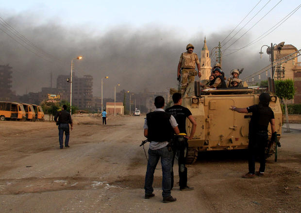Egyptian security forces take cover during clashes with suspected militants, not pictured, in the town of Kerdasa