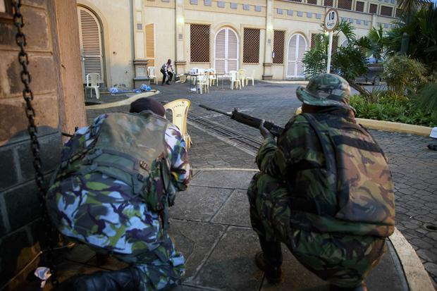 Kenya security personnel take cover outside the Westgate Mall