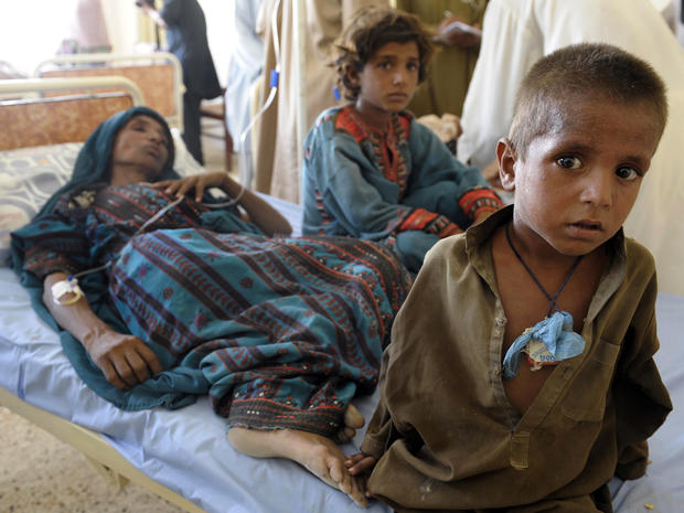 An injured Pakistani woman is surrounded by her children at a makeshift hospital in the earthquake-devastated Awaran, Pakistan, Sept. 25, 2013.