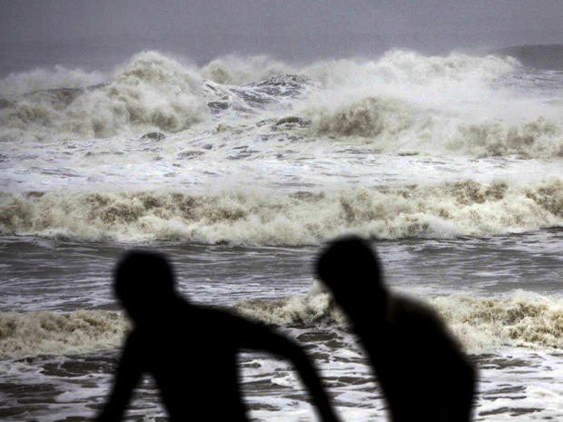 Indian people run for shelter following a cyclone warning at the Bay of Bengal coast in Gopalpur beach in Ganjam district, India, Oct. 12, 2013.