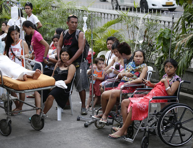 Patients stay outside a hospital to avoid aftershocks following a 7.2-magnitude earthquake that hit Cebu city in central Philippines, Tuesday, Oct. 15, 2013.